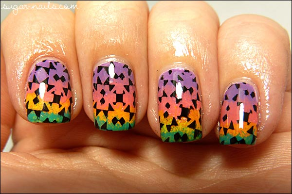 black kaleidoscope stamp on rainbow gradient nails