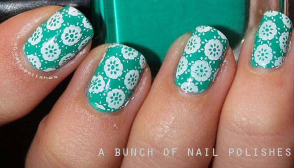 white flowers stamped on green nails